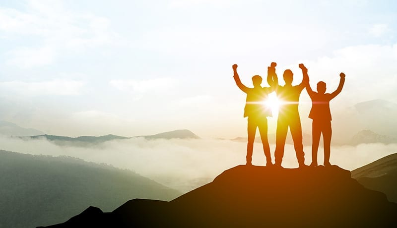 Silhouette of Business team show arm up on top of the mountain.